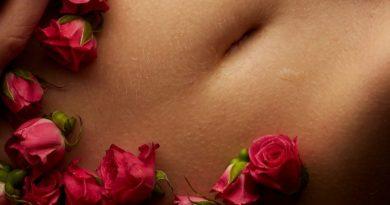 Bauch einer Frau mit Rosen und Hand